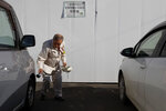 A worker checks the radiation level in the parking lot of a construction company Tuesday, Dec. 3, 2019, in Futaba, Fukushima prefecture, Japan. Most of the town is still inhabitable after the March 2011 earthquake and tsunami that crippled the nearby Fukushima Daiichi nuclear power plant. (AP Photo/Jae C. Hong)