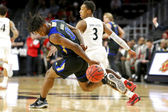 Tulsa guard Brandon Rachal (0) loses the ball behind his back as Cincinnati guard Mika Adams-Woods (3) defends during the first half of an NCAA college basketball game Wednesday, Jan. 8, 2020, in Cincinnati. (Kareem Elagazzar/The Cincinnati Enquirer via AP)