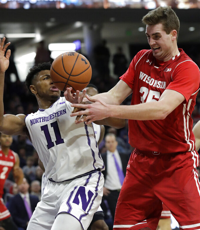 Wisconsin forward Nate Reuvers, right, battles for a rebound against Northwestern guard Anthony Gaines during the first half of an NCAA college basketball game Saturday, Feb. 23, 2019, in Evanston, Ill. (AP Photo/Nam Y. Huh)
