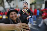 A supporter of Venezuela's President Nicolas Maduro holds a ceramic doll in his likeness outside the Supreme Court where he is being sworn-in for a second term in Caracas, Venezuela, Thursday, Jan. 10, 2019. Maduro was sworn in for a six-year term amid international calls for him to step down and a devastating economic crisis. (AP Photo/Ariana Cubillos)