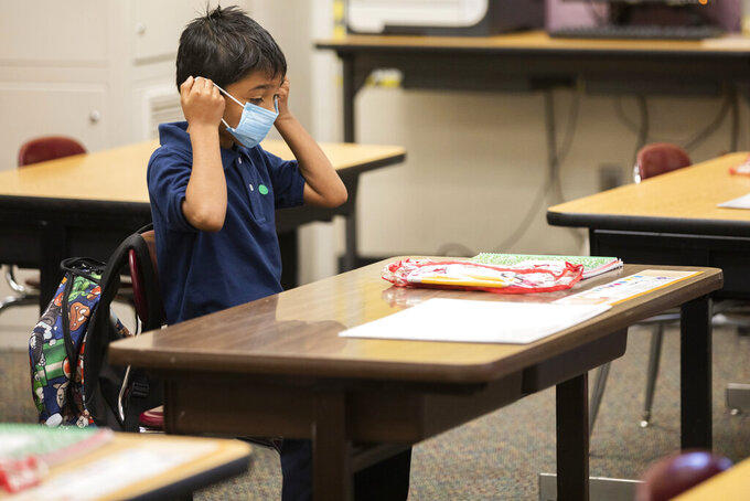 FILE - In this March 30, 2021, file photo, second grader Ernesto Beltran Pastrana puts on his face mask while attending class during the first day of partial in-person instruction at Garfield Elementary School in Oakland, Calif. Dozens of school districts around the country have eliminated requirements for students to wear masks, and many more are likely to ditch mask requirements before the next academic year. (Jessica Christian/San Francisco Chronicle via AP, File)
