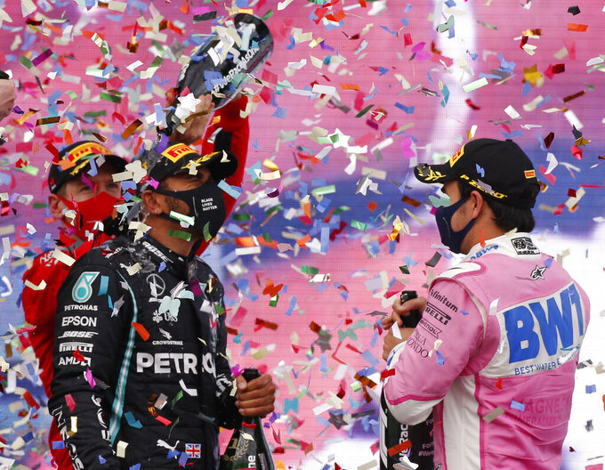 Third placed Ferrari driver Sebastian Vettel of Germany, left, pours champagne of race winner Mercedes driver Lewis Hamilton of Britain, as Racing Point driver Sergio Perez, right, of Mexico who finished second looks on the podium of the Formula One Turkish Grand Prix at the Istanbul Park circuit racetrack in Istanbul, Sunday, Nov. 15, 2020. (AP Photo/Kenan Asyali, Pool)