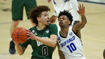 Ohio's Jason Preston (0) drives to the basket against Buffalo's Ronaldo Segu (10) during the first half of an NCAA college basketball game in the championship of the Mid-American Conference tournament, Saturday, March 13, 2021, in Cleveland. (AP Photo/Tony Dejak)