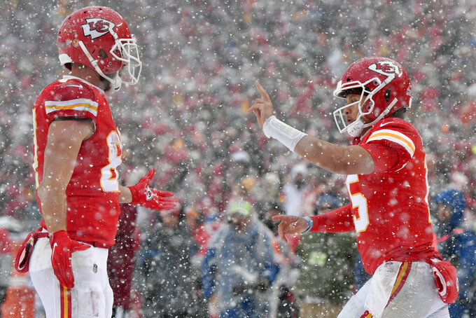 Kansas City Chiefs quarterback Patrick Mahomes, right, celebrates a touchdown by wide receiver Tyreek Hill with tight end Travis Kelce, left, during the second half of an NFL football game against the Denver Broncos in Kansas City, Mo., Sunday, Dec. 15, 2019. (AP Photo/Ed Zurga)