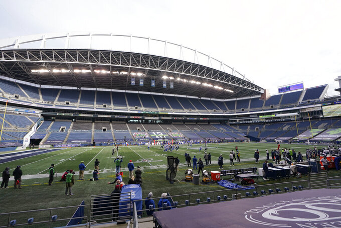 FILE - In this Jan. 9, 2021, file photo, the Seattle Seahawks play against the Los Angeles Rams in an otherwise empty stadium during the first half of an NFL wild-card playoff football game in Seattle.  The dip in revenue for the NFL during the pandemic has been substantial but not crippling. The biggest negative is revenues being on the low end of what was hoped because of limits on crowds in most NFL cities. (AP Photo/Ted S. Warren, File)