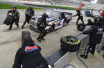 Sheldon Creed is tended to by pit crew during a NASCAR Truck Series auto race at Atlanta Motor Speedway, Saturday, Feb. 23, 2019, in Hampton, Ga. (AP Photo/John Amis)