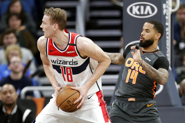 Washington Wizards center Anzejs Pasecniks (18) looks to pass the ball as he is defended by Orlando Magic guard D.J. Augustin (14) during the second half of an NBA basketball game Wednesday, Jan. 8, 2020, in Orlando, Fla. (AP Photo/John Raoux)