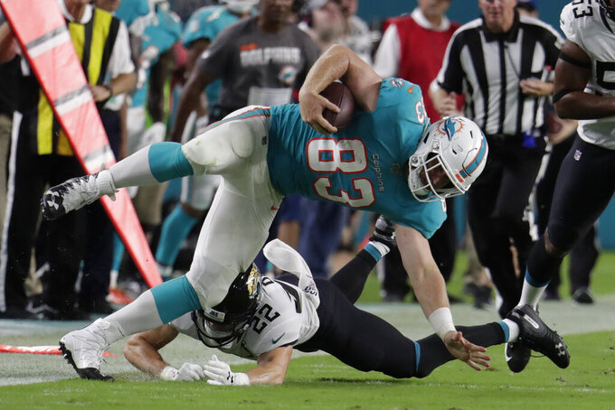 Miami Dolphins tight end Nick O'Leary (83) is taken down by Jacksonville Jaguars safety Cody Davis (22) during the second half of an NFL football preseason game Thursday, Aug. 22, 2019, in Miami Gardens, Fla. (AP Photo/Lynne Sladky)