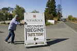 In this Wednesday, Nov. 6, 2019 photo, owner Ken Wilson rolls out a sign for passing motorists after opening a tasting area at his wildfire incinerated Soda Rock Winery in Healdsburg, Calif. If you're worried that wildfires might have created shortages of Northern California's 2019 Cabernet Sauvignon, or even just imparted it with an undesirable smoky flavor, you can relax. The wine is just fine. For now. (AP Photo/Eric Risberg)