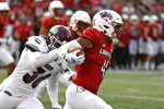 Louisville's Braden Smith (4) evades the grasp of y Eastern Kentucky's Kyle Bailey (36) during the first half of an NCAA college football game in Louisville, Ky., Saturday, Sept. 11, 2021. (AP Photo/Timothy D. Easley)