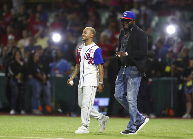 Retired Boston Red Sox player David Ortiz of the Dominican Republic, affectionately known as Big Papi, right, and Puerto Rican singer Ozuna, walk onto the field for the opening pitch of the Caribbean Series baseball game between Dominican Republic and Puerto Rico, in San Juan, Puerto Rico, Wednesday, Feb. 5, 2020.(AP Photo/Fernando Llano)