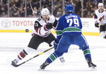 Arizona Coyotes' Vinnie Hinostroza (13) flips the puck past Vancouver Canucks' Ashton Sautner during the first period of an NHL hockey game Thursday, Feb. 21, 2019, in Vancouver, British Columbia. (Darryl Dyck/The Canadian Press via AP)