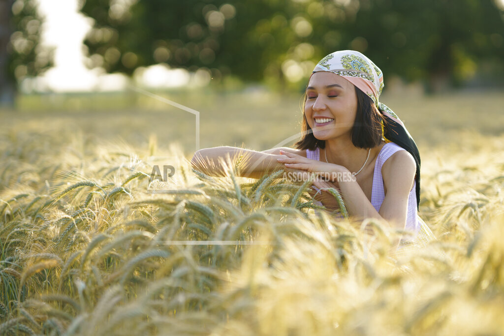 Smiling young woman standing with eyes closed enjoying in wheat field