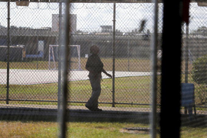 FILE — In this Sept. 26, 2019 file photo, a guard walks on a path between yards during a media tour inside the Winn Correctional Center, in Winnfield, La. The number of detainees nationwide has more than doubled since the end of February 2021, to nearly 27,000, according to recent data from U.S. Immigration and Customs Enforcement. (AP Photo/Gerald Herbert, File)