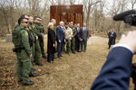 A section of border wall, used for training, is visible behind Vice President Mike Pence, center, and Homeland Security Secretary Kirstjen Nielsen, center left, as they pose for a photograph with Border Patrol agents following a border wall training demonstration at the U.S. Customs and Border Protection Advanced Training Facility in Harpers Ferry, W.Va., Wednesday, March 13, 2019. (AP Photo/Andrew Harnik)