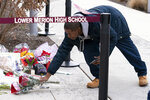 Shaheem Cochran-Todd of North Philadelphia drops off flowers in remembrance to Kobe Bryant at a small memorial at the entrance of the Bryant Gymnasium at Lower Merion High School, Monday, Jan. 27, 2020, in Wynnewood, Pa. Bryant, the 18-time NBA All-Star who won five championships and became one of the greatest basketball players of his generation during a 20-year career with the Los Angeles Lakers, died in a helicopter crash Sunday, Jan. 26. (AP Photo/Chris Szagola)