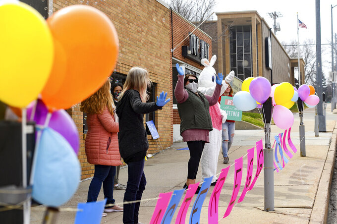 Volunteers wave at passing cars, encouraging families to meet the Easter Bunny from their vehicles on Saturday, April 11, 2020 on the curb of New Life Church in downtown Sioux Falls, S.D. Churches around the city are finding social distancing-safe methods of celebrating Easter during the coronavirus pandemic. (Erin Bormett/The Argus Leader via AP)