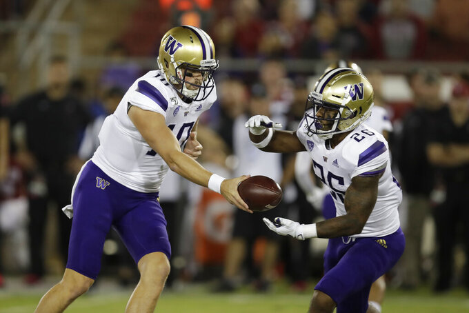 Washington quarterback Jacob Eason, left, hands the ball off to Salvon Ahmed (26) during the first half of an NCAA college football game against Saturday, Oct. 5, 2019, in Stanford, Calif. (AP Photo/Ben Margot)