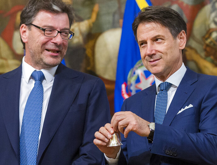 Italy's Prime Minister Giuseppe Conte, right, flanked by former undersecretary Giancarlo Giorgetti of the Northern League, poses with the bell that traditionally opens the meeting of the cabinet as he starts the first cabinet meeting of his new government at Chigi Palace in Rome, Thursday, Sept. 5, 2019. Italian Premier Giuseppe Conte forged a new coalition government Wednesday that teams up the populist 5-Star Movement and center-left Democrats in an unusual alliance of rivals to banish for now the specter of early election that likely could have seen the triumph of Italy's fast-rising right-wing forces. (AP Photo/Domenico Stinellis)