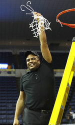 Georgia State head coach Ron Hunter holds a piece of the net after playing Texas-Arlington in the NCAA college basketball championship game of the Sun Belt Conference men's tournament in New Orleans, Sunday, March 17, 2019. Georgia State won 73-64. (AP Photo/Tyler Kaufman)