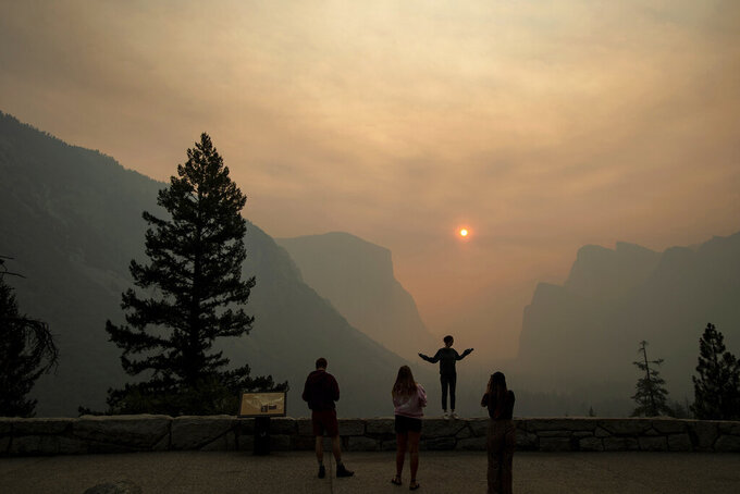 FILE - In this July 25, 2018 file photo, Hannah Whyatt poses for a friend's photo as smoke from the Ferguson Fire fills Yosemite Valley in Yosemite National Park, Calif. Wildfires burning in the U.S. this summer have upended plans for countless outdoor adventures. Campers, hikers, rafters and other outdoor enthusiasts have had to scrap or change plans or endure awful smoke. (AP Photo/Noah Berger, File)