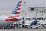 An American Airlines plane at left, leaves a gate area near an Alaska Airlines plane, Thursday, Feb. 13, 2020, at Seattle-Tacoma International Airport in Seattle. American Airlines and Alaska Airlines announced Thursday that they will cooperate more closely on West Coast service, including new American flights from Seattle to India's technology hub in Bangalore. (AP Photo/Ted S. Warren)