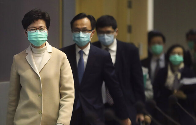 Hong Kong Chief Executive Carrie Lam, front, and other government officials wear protective face masks before a press conference in Hong Kong, Friday, Jan. 31, 2020. China has moved to lock down at least three big cities in an unprecedented effort to contain the deadly new virus that has sickened hundreds of people and spread to other parts of the world. (AP Photo/Achmad Ibrahim)