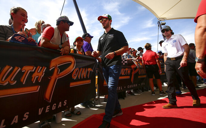 Daniel Suarez, center, and Ryan Blaney, right, walk by fans before a NASCAR Cup Series auto race at the Las Vegas Motor Speedway on Sunday, Sept. 15, 2019. (AP Photo/Chase Stevens)