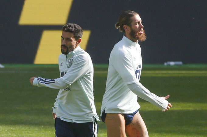 Spain's Sergio Ramos, right, and Jesus Navas warm up during a training session at the Olimpiyskiy Stadium in Kyiv, Ukraine, Monday, Oct. 12, 2020. Ukraine will play a UEFA Nations League soccer match against Spain on Tuesday. (AP Photo/Efrem Lukatsky)