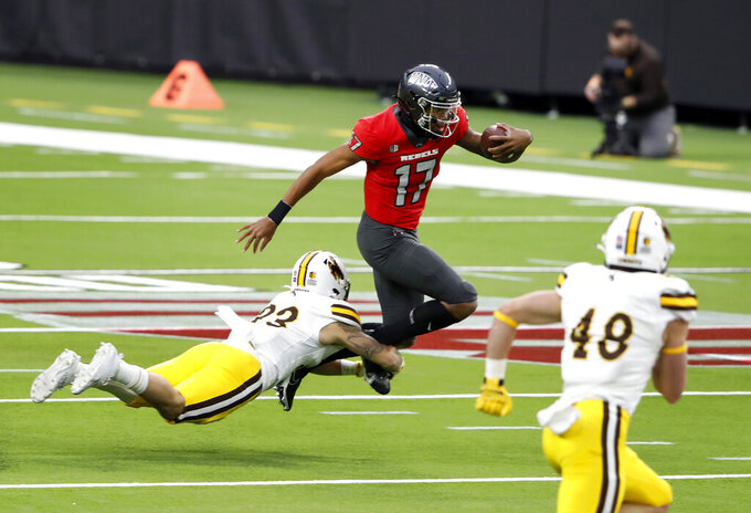 Wyoming linebacker Charles Hicks (33) dives for a tackle on UNLV quarterback Doug Brumfield (17) during the first half of an NCAA college football game in Las Vegas on Friday, Nov. 27, 2020. (Steve Marcus/Las Vegas Sun via AP)