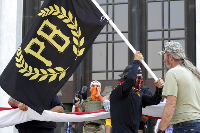 "FILE - In this Sept. 7, 2020 photo, a protester carries a Proud Boys banner, symbol of a right-wing group, while other members start to unfurl a large U.S. flag in front of the Oregon State Capitol in Salem, Ore. President Donald Trump didn't condemn white supremacist groups and their role in violence in some American cities this summer. Instead, he said the violence is a ""left-wing"