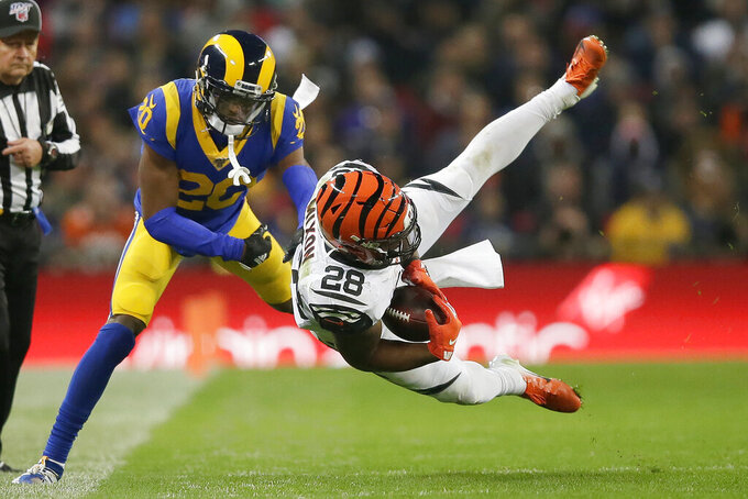 Cincinnati Bengals running back Joe Mixon (28) is tackled by Los Angeles Rams cornerback Troy Hill (20) during the second half of an NFL football game, Sunday, Oct. 27, 2019, at Wembley Stadium in London. (AP Photo/Tim Ireland)
