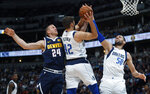 Denver Nuggets forward Mason Plumlee competes for a rebound with Dallas Mavericks forward Maximilian Kleber and center Salah Mejri, right, during the first half of an NBA basketball game Thursday, March 14, 2019, in Denver. (AP Photo/David Zalubowski)