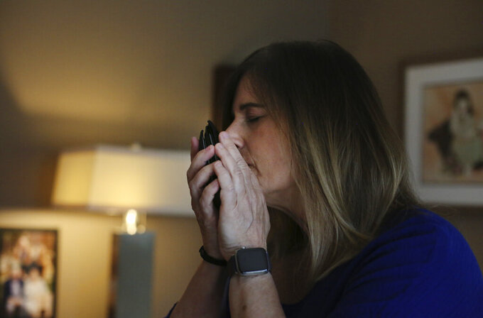 Michelle Pepe tries to smell her late father's wallet while going through his belongings one year after he died of the coronavirus, in Sharon, Mass., on Wednesday, April 14, 2021. After contracting the virus herself, Pepe lost and has not regained her sense of smell. She keeps her father's belongings in hopes that one day it comes back and she can smell him again. (AP Photo/Jessie Wardarski)