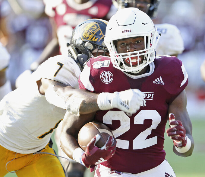 Mississippi State running back Lee Witherspoon (22) drags Southern Mississippi defensive back Ty Williams (7) across the goal line for a touchdown in the second half of an NCAA college football game Saturday, Sept. 7, 2019, in Starkville, Miss.. Miss. St. won 38-15. (AP Photo/Jim Lytle)