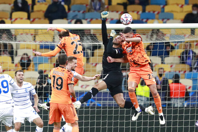 Dynamo Kyiv's goalkeeper Heorhiy Bushchan jumps for the ball with Juventus' Merih Demiral, right, during the Champions League, group G, soccer match between Dynamo Kyiv and Juventus at the Olimpiyskiy Stadium in Kyiv, Ukraine, Tuesday, Oct. 20, 2020. (Valentyn Ogirenko/Pool via AP)