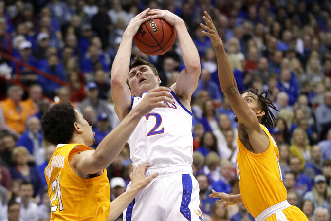 Kansas guard Christian Braun, center, rebounds between Tennessee forward Olivier Nkamhoua, left, and guard Jalen Johnson, right, during the first half of an NCAA college basketball game in Lawrence, Kan., Saturday, Jan. 25, 2020. (AP Photo/Orlin Wagner)
