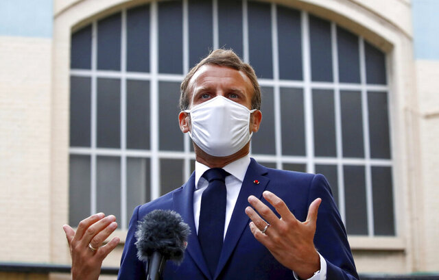 French President Emmanuel Macron, wearing a protective face mask, gestures as he speaks to the media as he visits a site of pharmaceutical group Seqens, in Villeneuve-la-Garenne, near Paris, Friday Aug. 28, 2020. French President Emmanuel Macron urged European neighbors Friday to better coordinate cross-border virus restrictions as infections resurge – and as multiple countries impose tests or quarantines on visitors from France. (Christian Hartmann/Pool Photo via AP)