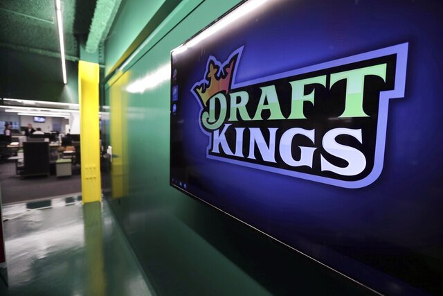 FILE - In this May 2, 2019, file photo, the DraftKings logo is displayed at the sports betting company headquarters in Boston.  DraftKings shares jumped 4% in morning trading, Wednesday, Sept. 2, 2020 after announcing that basketball legend Michael Jordan would take an ownership stake in the company in exchange for becoming a special adviser to the sports betting site.  (AP Photo/Charles Krupa, File)