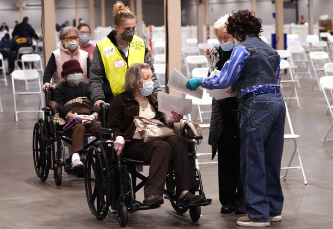 FILE - In this Jan. 20, 2021, file photo, elderly wait in wheel chairs as their paper work is checked before receiving a COVID-19 vaccine at a Dallas County mass vaccination site at Fair Park in Dallas. As the nation's COVID-19 vaccination campaign accelerates, governors, public health directors and committees advising them are holding key discussions behind closed doors, including debates about who should be eligible for the shots and how to best distribute them. (AP Photo/LM Otero, File)