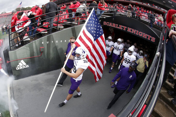 Northwestern place kicker Drew Luckenbaugh holds a U.S. flag before leading his team onto the field for an NCAA college football game against Rutgers, Saturday, Oct. 20, 2018, in Piscataway, N.J. (AP Photo/Julio Cortez)