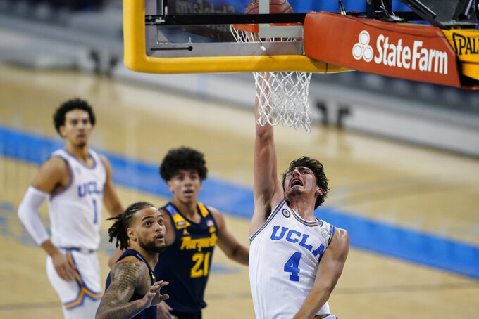 UCLA guard Jaime Jaquez Jr. , right, shoots while defended by Marquette forward Theo John, front left, during the first half of an NCAA college basketball game Friday, Dec. 11, 2020, in Los Angeles. (AP Photo/Ashley Landis)