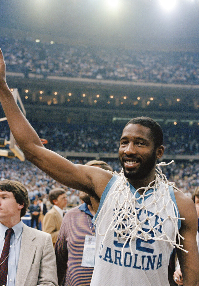 FILE - In this March 29, 1982, file photo, North Carolina's James Worthy wears the net after it was cut down following North Carolina defeating Georgetown 68-62 in the NCAA college basketball Final Four championship in New Orleans. Worthy won the duel of dunks with Georgetown's Pat Ewing, scoring a career-high 28 points and winning the Most Outstanding Player award. (AP Photo/File)