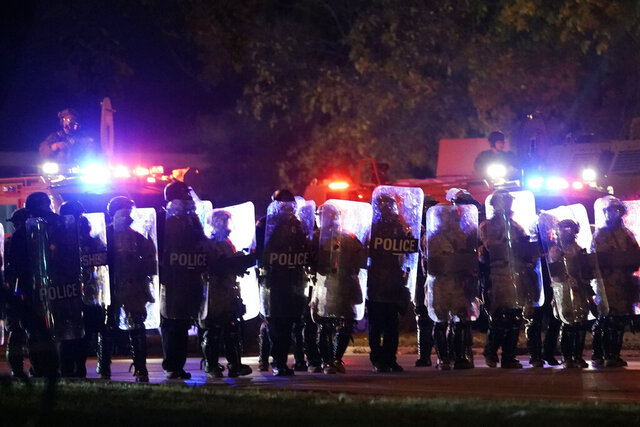 Police in riot gear line up Friday, Oct. 9, 2020, in Wauwatosa, Wis. On Wednesday, District Attorney John Chisholm refused to issue charges against Wauwatosa Police Officer Joseph Mensah for the Feb. 2 fatal shooting of 17-year-old Alvin Cole at Mayfair Mall. (AP Photo/Morry Gash)
