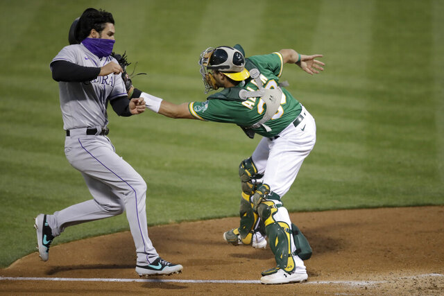 Colorado Rockies' Nolan Arenado, left, scores against Oakland Athletics catcher Austin Allen in the fifth inning of a baseball game Tuesday, July 28, 2020, in Oakland, Calif. (AP Photo/Ben Margot)