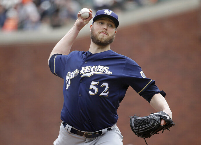 FILE - In this Saturday, June 15, 2019 file photo, Milwaukee Brewers pitcher Jimmy Nelson (52) throws to a San Francisco Giants batter during the second inning of a baseball game in San Francisco. Right-hander Jimmy Nelson and the Los Angeles Dodgers agreed Tuesday, Jan. 7, 2020 to a $1.25 million, one-year contract, an incentive-laden deal that could be worth $13.25 million over two seasons. In what's become a familiar refrain, the Dodgers arrive at camp still looking for their first World Series championship since 1988. After losing in two straight World Series, they were ousted by Washington in five games in the NL Division Series last fall. (AP Photo/Jeff Chiu, File)