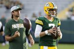 Green Bay Packers' Aaron Rodgers watches as Kurt Benkert warms up before a preseason NFL football game against the Houston Texans Saturday, Aug. 14, 2021, in Green Bay, Wis. (AP Photo/Mike Roemer)