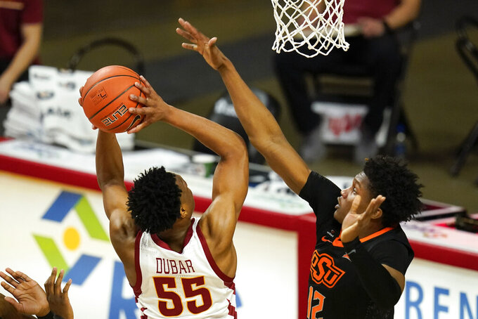 Oklahoma State forward Matthew-Alexander Moncrieffe tries to block a shot by Iowa State guard Darlinstone Dubar (55) during the second half of an NCAA college basketball game, Monday, Jan. 25, 2021, in Ames, Iowa. Oklahoma State won 81-60. (AP Photo/Charlie Neibergall)