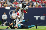 Houston Texans running back Mark Ingram II (2) rushes for a first down as Jacksonville Jaguars safety Andrew Wingard defends during the second half of an NFL football game Sunday, Sept. 12, 2021, in Houston. (AP Photo/Sam Craft)
