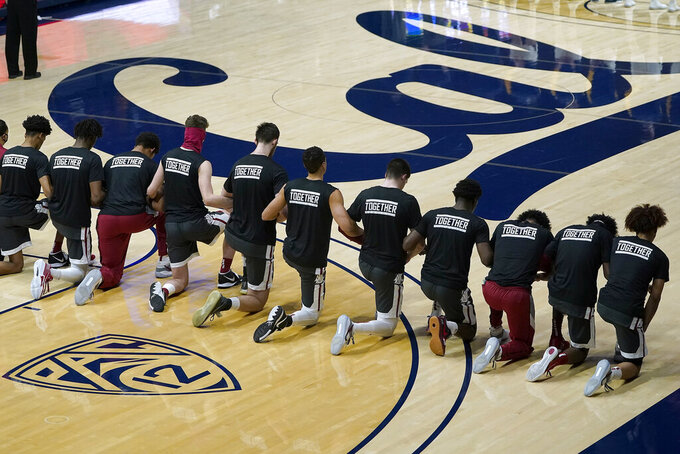 Washington State players kneel during the national anthem before an NCAA college basketball game against California, Thursday, Jan. 7, 2021, in Berkeley, Calif. (AP Photo/Tony Avelar)